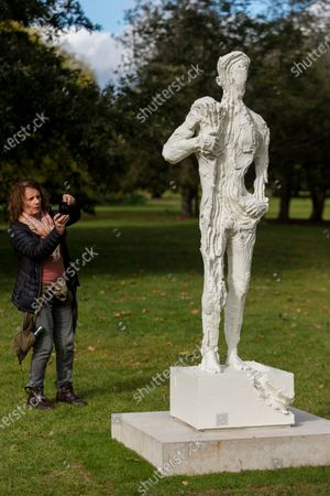 """Stock Picture of A woman views """"Untitled 1 (Bodybuilders)"""", 2015, by David Altmejd at Frieze Sculpture, an annual exhibition of outdoor works by international artists in Regent's Park. The works are on display to the public until 18 October."""