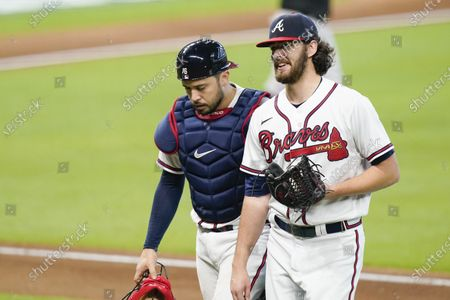Atlanta Braves' Ian Anderson, right, an catcher Travis d'Arnaud walk to the dugout during the fourth inning in Game 2 of a baseball National League Division Series against the Miami Marlins, in Houston