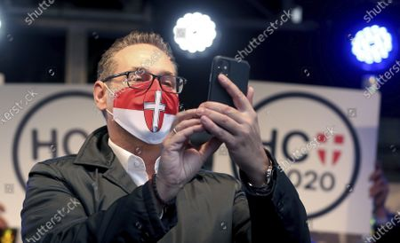 Heinz-Christian Strache with face mask, former leader of the right-wing Freedom Party, FPOE, looks at his cellphone at a closing rally for his party Team Strache ahead to the local elections in Vienna, Austria