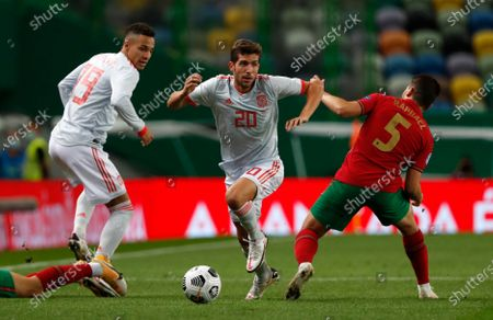 Spain's Sergi Roberto, center, takes the ball past Portugal's Raphael Guerreiro during the international friendly soccer match between Portugal and Spain at the Jose Alvalade stadium in Lisbon