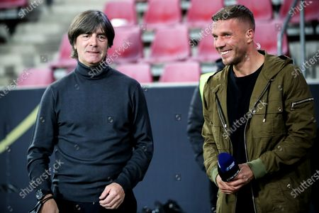 Germany's head coach Joachim Loew (L) and former German national soccer player Lukas Podolski (R) react prior to the international friendly soccer match between Germany and Turkey at Rheinenergiestadion in Cologne, Germany, 07 October 2020.
