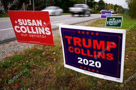 """TRUMP COLLINS 2020"""" sign, right, paid for by the Maine Democratic Party, stands alongside a """"Susan Collins our senator"""" sign, paid for by the Maine Republican Party, in Freeport, Maine. Sen. Collins, R-Maine, is being challenged by Democrat Sara Gideon"""