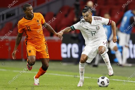 Dutch player Georginio Wijnaldum (L) and Jesus Manuel Corona of Mexico in action during the international friendly soccer match between the Netherlands and Mexico at Johan Cruyff Arena in Amsterdam, the Netherlands, 07 October 2020.