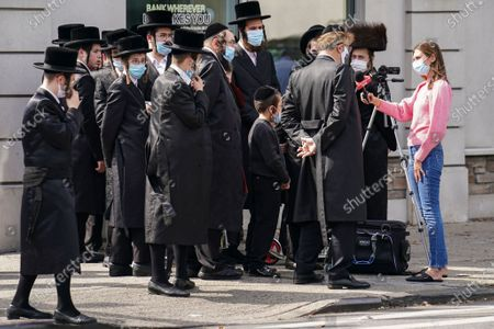 Members of the Jewish Orthodox community gather to listen to an interview conducted by a journalist on a street corner, in the Borough Park neighborhood of the Brooklyn borough of New York. Gov. Andrew Cuomo moved to reinstate restrictions on businesses, houses of worship and schools in and near areas where coronavirus cases are spiking. Many neighborhoods that stand to be affected are home to large enclaves of Orthodox Jews