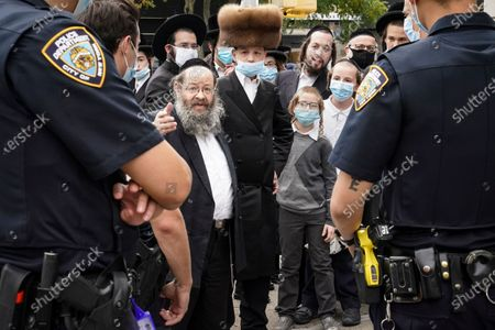 Members of the Jewish Orthodox community speak with NYPD officers on a street corner, in the Borough Park neighborhood of the Brooklyn borough of New York. Gov. Andrew Cuomo moved to reinstate restrictions on businesses, houses of worship and schools in and near areas where coronavirus cases are spiking. Many neighborhoods that stand to be affected are home to large enclaves of Orthodox Jews