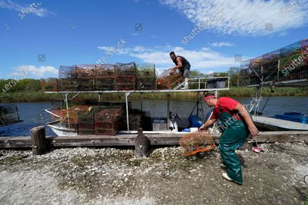 Jule Chaisson, foreground, and Brian Dufrene, Jr. pull their crab traps from Bayou Dularge in anticipation of Hurricane Delta, expected to arrive along the Gulf Coast later this week, in Theriot, La