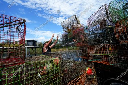 Brian Dufrene loads his crab traps on a trailer after pulling them from Bayou Dularge in anticipation of Hurricane Delta, expected to arrive along the Gulf Coast later this week, in Theriot, La., . Dufrene says he's pulled around 1,000 traps over the last three days