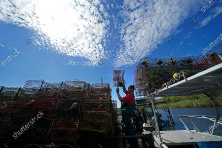 Jule Chaisson, stacks his crab traps on a trailer after pulling them from Bayou Dularge in anticipation of Hurricane Delta, expected to arrive along the Gulf Coast later this week, in Theriot, La