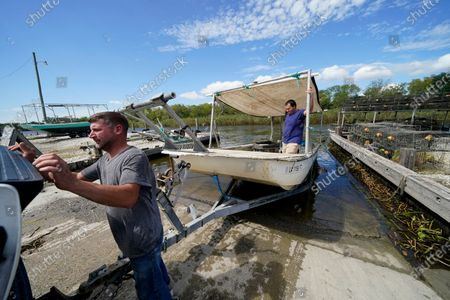 Charles Russ and Allan Bergeron, right, pull their boat from the water after pulling their crab traps from Bayou Dularge in anticipation of Hurricane Delta, expected to arrive along the Gulf Coast later this week, in Theriot, La