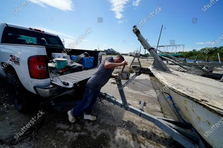 Stock Photo of Charles Russ pulls their boat from the water after pulling his crab traps from Bayou Dularge in anticipation of Hurricane Delta, expected to arrive along the Gulf Coast later this week, in Theriot, La