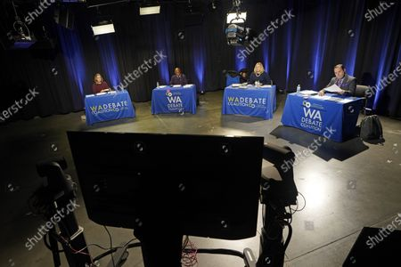 Reporters who will be serving as moderators for an evening debate between Washington gubernatorial candidates Gov. Jay Inslee, a Democrat, and Loren Culp, a Republican, take part in a walk-through and sound check, at the studios of TVW in Olympia, Wash. Due to concerns over COVID-19, each candidate will be taking part in the debate from individual rooms separate from the moderators, who will only see the candidates on a video monitor. From left, the moderators are Brandi Kruse, Q13; Essex Porter, KIRO7; Melissa Santos, Crosscut / KCTS9; and Chris Daniels, KING5
