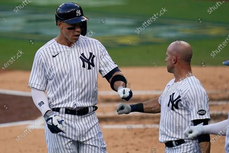 New York Yankees' Aaron Judge, left, bumps fists with Brett Gardner after Gardner scored on Judge's sacrifice flyout hit against the Tampa Bay Rays during the third inning in Game 3 of a baseball American League Division Series, in San Diego