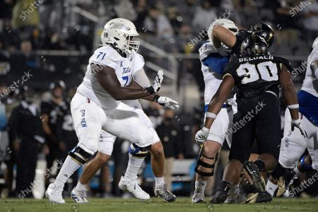 Tulsa offensive tackle Chris Paul (71) sets up to block in front of Central Florida defensive lineman Chris DeLoach (90) during the first half of an NCAA college football game, in Orlando, Fla