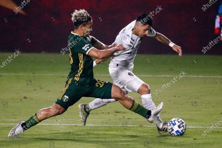 Portland Timbers defender Pablo Bonilla, left, and LA Galaxy forward Cristian Pavon vie for the ball during the second half of an MLS soccer match in Carson, Calif., . The Timbers won 6-3