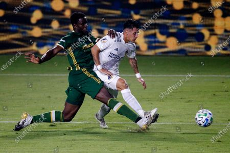 Portland Timbers defender Larrys Mabiala, left, and LA Galaxy forward Cristian Pavon compete for the ball during the second half of an MLS soccer match in Carson, Calif., . The Timbers won 6-3