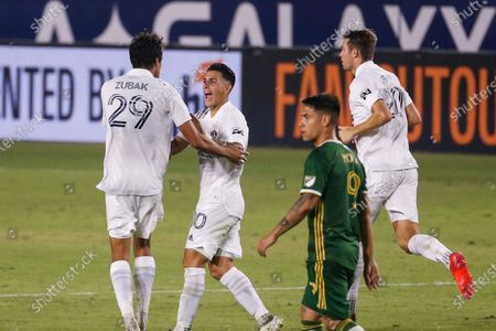 Galaxy forwards Cristian Pavon (10) of Argentina, celebrates after Ethan Zubak (29) scoring a goal during an MLS soccer match between LA Galaxy and Portland Timbers in Carson, Calif., . The Timbers won 6-3