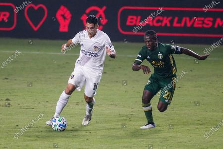 Galaxy forward Cristian Pavon (10) of Argentina, and Portland Timbers midfielder Diego Chara (21) of Colombia, in actions during an MLS soccer match between LA Galaxy and Portland Timbers in Carson, Calif., . The Timbers won 6-3