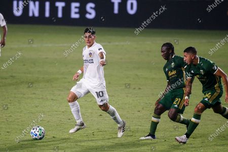Galaxy forward Cristian Pavon (10) of Argentina, and Portland Timbers midfielder Diego Chara (21) of Colombia, and Portland Timbers midfielder Marvin Loria (44) of Costa Rica, in actions during an MLS soccer match between LA Galaxy and Portland Timbers in Carson, Calif., . The Timbers won 6-3