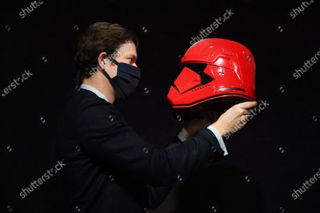 A Bonham's staff member with a Sith Trooper Helmet from Star Wars: The Rise Of Skywalker (2019), donated to the cause by Lucasfilm. The helmet was created by BAFTA award-winning costume designer Michael Kaplan in a striking red colour, distinguishing the new stormtroopers from the classic, white-armoured forces beloved by previous generations, est. £20,000-30,000.    All proceeds of the sale will go to support BAFTA's year-round charitable activity, which is focused on finding and supporting new and existing talent in the UK and internationally, and breaking down the barriers that make it hard to build careers in the film, games and television industries.