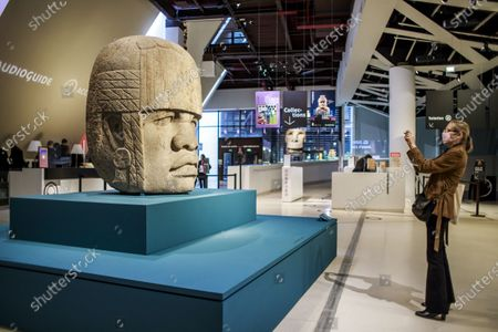 A visitor takes a picture of the colossal Olmec head 'Monument 4' of San Lorenzo (1,200-900 BC) during a press preview of the exhibition 'The Olmecs and the Civilizations from the Gulf of Mexico' at the Quai Branly Museum-Jacques Chirac, a museum featuring indigenous art and cultures of Africa, Asia, Oceania and the Americas, in Paris, France, 08 October 2020. The exhibition opens to the public on 09 October 2020 to 25 July 2021.
