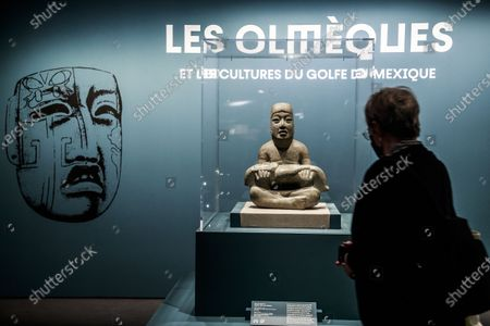 A visitor looks at a male sculpture on display during a press preview of the exhibition 'The Olmecs and the Civilizations from the Gulf of Mexico' at the Quai Branly Museum-Jacques Chirac, a museum featuring indigenous art and cultures of Africa, Asia, Oceania and the Americas, in Paris, France, 08 October 2020. The exhibition opens to the public on 09 October 2020 to 25 July 2021.