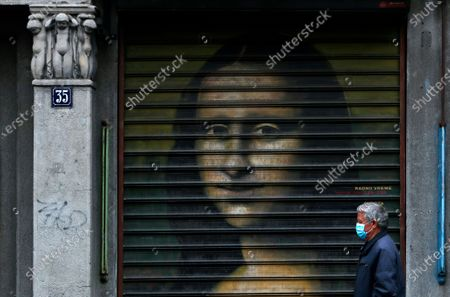 Man wearing a mask to protect against coronavirus walks by closed shop, with the image of Mona Lisa on the shutters, in downtown Belgrade, Serbia