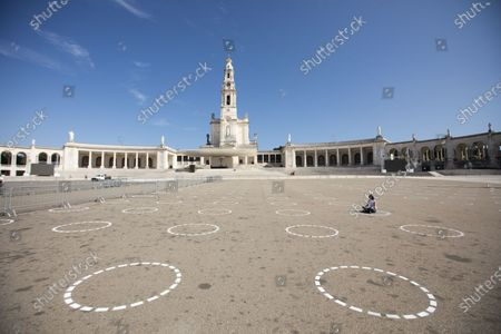 A pilgrims sits in one of painted circles that delimit the area and distance between pilgrims in the Marian shrine Fatima Sanctuary, Fatima, Ourem, portugal, 08 October 2020. The shrine enclosure features painted circles that delimit the area and distance between pilgrims in the Fatima shrine enclosure on the next pilgrimage to this Marian shrine. According to the plan already approved by the Directorate General of Health, the October pilgrimage will be subject to strong restrictions, and no more than six thousand people should be allowed to enter the enclosure as a measure to prevent the coronavirus pandemic.
