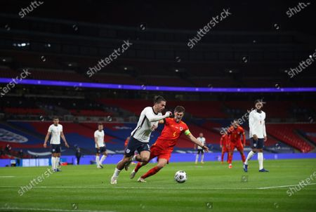 England's Jack Grealish, left, tries to dribble past Wales' Ben Davies, right, during the international friendly soccer match between England and Wales at Wembley stadium in London