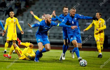 Iceland's Aron Gunnarsson, left, Kari Arnason, centre, and Ragnar Sigurdsson clear the ball during the Euro 2020 playoff semifinal soccer match between Iceland and Romania in Reykjavik, Iceland