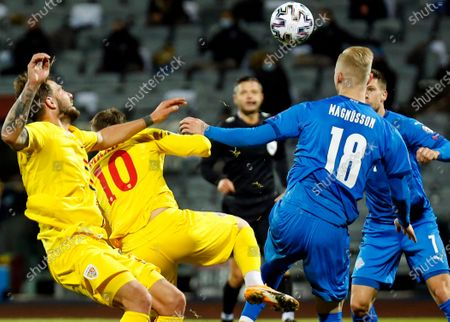Romania's Alexandru Maxim, left and Iceland's Hordur Bjorgvin Magnusson, right, battle for the ball during the Euro 2020 playoff semifinal soccer match between Iceland and Romania in Reykjavik, Iceland