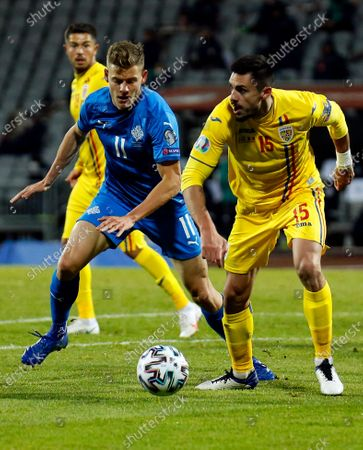 Romania's Andrei Burca, right, is challenged by Iceland's Alfred Finnbogason, center, during the Euro 2020 playoff semifinal soccer match between Iceland and Romania in Reykjavik, Iceland