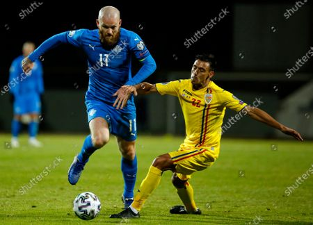 Iceland's Aron Gunnarsson, left, gets past Romania's Camora, right, during the Euro 2020 playoff semifinal soccer match between Iceland and Romania in Reykjavik, Iceland
