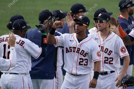Houston Astros manager Dusty Baker Jr., left, celebrates with Michael Brantley (23), Josh Reddick (22) and others after the Astros defeated the Oakland Athletics in Game 4 of a baseball American League Division Series in Los Angeles
