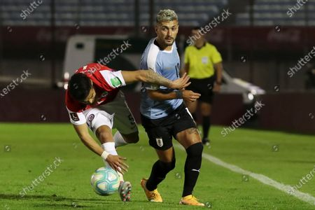 Chile's Paulo Diaz, left, and Uruguay's Giorgian De Arrascaeta vie for the ball during a qualifying soccer match for the FIFA World Cup Qatar 2022 at the Centenario stadium in Montevideo, Uruguay