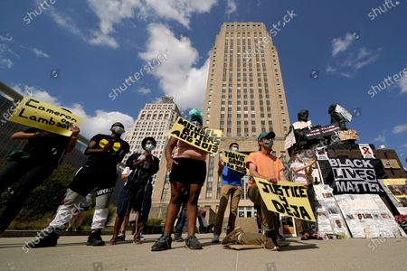 Protesters hold signs outside city hall, in Kansas City, Mo., demanding the resignation of an officer who knelt on the back of nine-months-pregnant Black woman, Deja Stallings, while arresting her the previous week, and Police Chief Rick Smith