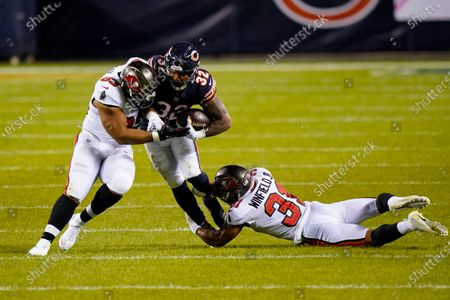 Chicago Bears running back David Montgomery (32) is tackled by Tampa Bay Buccaneers free safety Jordan Whitehead (33) and defensive end Ndamukong Suh (93) in the first half of an NFL football game in Chicago