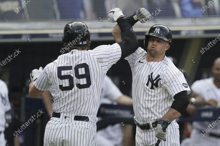 New York Yankees first baseman Luke Voit (59) celebrates with Brett Gardner, left, after Voit hit a solo home run against the Tampa Bay Rays during the second inning in Game 4 of a baseball American League Division Series, in San Diego