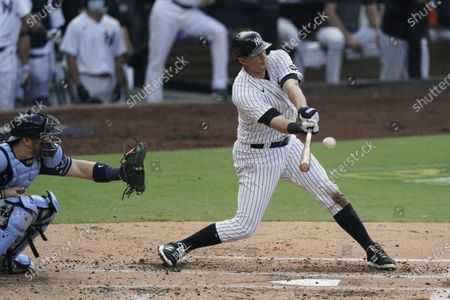 New York Yankees' DJ LeMahieu hits a sacrifice fly to score Brett Gardner as Tampa Bay Rays catcher Mike Zunino looks on during the second inning in Game 4 of a baseball American League Division Series, in San Diego