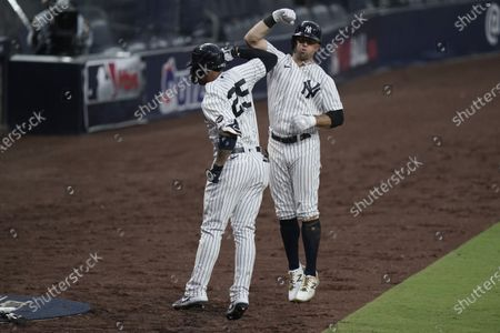 New York Yankees' Gleyber Torres, left, celebrates with Brett Gardner, right, after Torres hit a two-run home run to score Gardner during the sixth inning in Game 4 of a baseball American League Division Series against the Tampa Bay Rays, in San Diego
