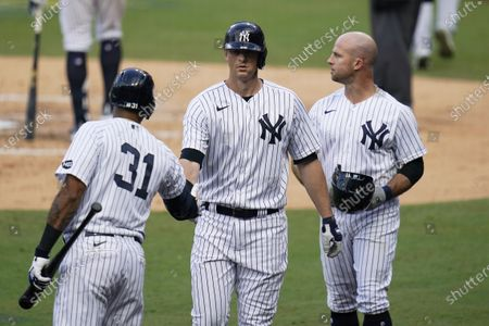 New York Yankees' Brett Gardner, right, stands with Aaron Hicks (31) and DJ LeMahieu, center, after Gardner scored on a sacrifice fly hit by Garner against the Tampa Bay Rays during the second inning in Game 4 of a baseball American League Division Series, in San Diego