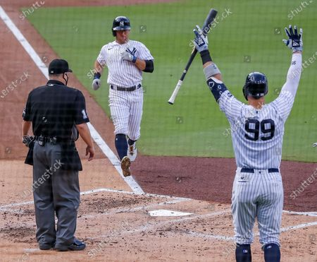 Stock Photo of New York Yankees left fielder Brett Gardner (C) scores as New York Yankees right fielder Aaron Judge (R) reacts and home plate umpire Todd Tichenor looks on in the second inning of the American League Division Series playoff game four between the Tampa Bay Rays and the New York Yankees at Petco Park in San Diego, California, USA, 08 October 2020.