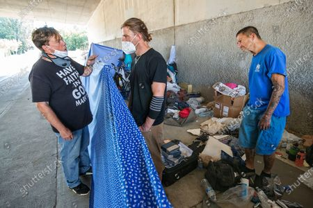 Pastor Donald Dermit, left, of HelpingHandUps, a homeless outreach provider based in Orange County, talks with Andrew Carolus, center and Robin Lee, right, at a homeless encampment on Fallbrook Ave. underneath the 101 freeway in Woodland Hills. Carolus lives at this encampment, and Lee was visiting from another homeless encampment. Los Angeles has reached a pivotal moment in its efforts to house people living on its streets. Hotels for homeless people are coming off line at the same moment that the city is beginning to implement a plan to bring people off the street.(Mel Melcon / Los Angeles Times)