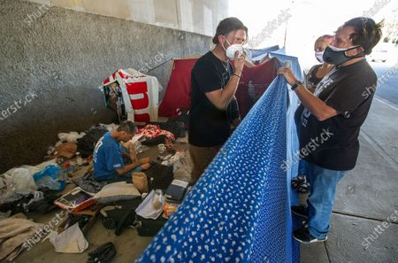 Left to right-Andrew Carolus, 37, who is homeless, talks with Farah Bailey and Pastor Donald Dermit of HelpingHandUps, at a homeless encampment on Fallbrook Ave. underneath the 101 freeway in Woodland Hills. HelpingHandUps is a homeless outreach provider based in Orange County. Los Angeles has reached a pivotal moment in its efforts to house people living on its streets. Hotels for homeless people are coming off line at the same moment that the city is beginning to implement a plan to bring people off the street.(Mel Melcon / Los Angeles Times)