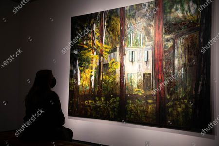 """A member of staff looks at """"Boiler House"""" (estimated value £13 Million) by Peter Doig during a press preview at Christie's King Street for the Post-War and contemporary art evening auction part of the 20th Century Paris to London sale series."""