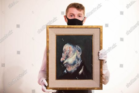 """A member of staff looks at """"Head of Man"""" (estimated value £4 million-£6 million) by Francis Bacon during a press preview at Christie's King Street for the Post-War and contemporary art evening auction part of the 20th Century Paris to London sale series."""