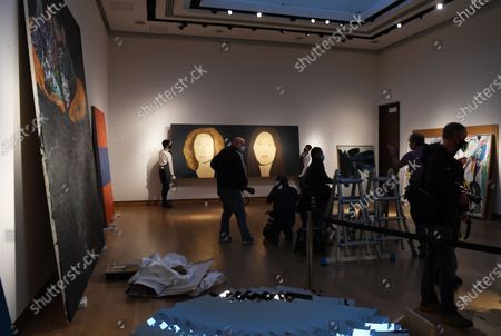 A Christie's employee poses for photographers next to a painting by US artist Alex Katz, entitled 'Marina and Bettina,' in London, Britain, 09 October 2020. The artwork is expected to fetch 400,000-600,000 GBP (about 438,000-658,000 EUR) at Christie's Post-War and Contemporary Art sale on 22 October.