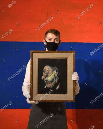 Stock Picture of A Christie's employee poses for photographers holding a painting by British artist Francis Bacon, entitled 'Head of Man,' in London, Britain, 09 October 2020. The artwork is expected to fetch 4-6 milion GBP (about 4.386.000-6.580.000 EUR) at Christie's Post-War and Contemporary Art sale on 22 October.