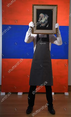 Stock Image of A Christie's employee poses for photographers holding a painting by British artist Francis Bacon, entitled 'Head of Man,' in London, Britain, 09 October 2020. The artwork is expected to fetch 4-6 milion GBP (about 4.386.000-6.580.000 EUR) at Christie's Post-War and Contemporary Art sale on 22 October.