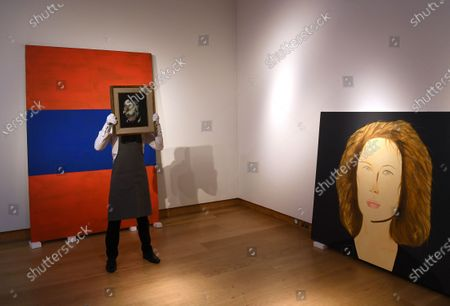 A Christie's employee poses for photographers holding a painting by British artist Francis Bacon, entitled 'Head of Man,' in London, Britain, 09 October 2020. The artwork is expected to fetch 4-6 milion GBP (about 4.386.000-6.580.000 EUR) at Christie's Post-War and Contemporary Art sale on 22 October.