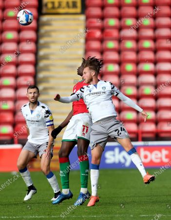 Stock Photo of Ben Stevenson of Colchester United challenges for the aerial ball with Elijah Debayo of Walsall; Bescot Stadium, Walsall, West Midlands, England; English Football League Two, Walsall FC versus Colchester United.